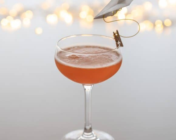A paper plane cocktail in a coupe glass, garnished with a mini paper plane, with lights twinkling in the background.