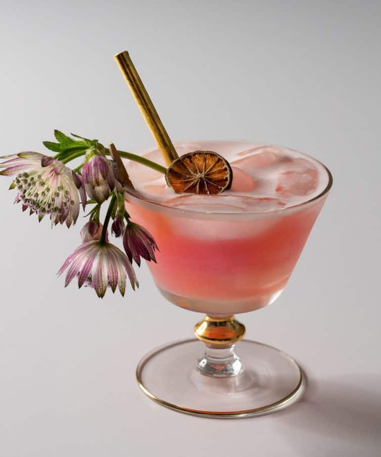 A Chinese fizz cocktail garnished with flowers, a citrus wheel, and a straw.