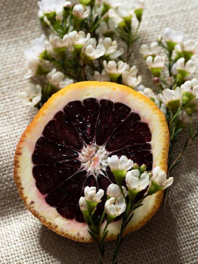 A halved blood orange with white flowers.