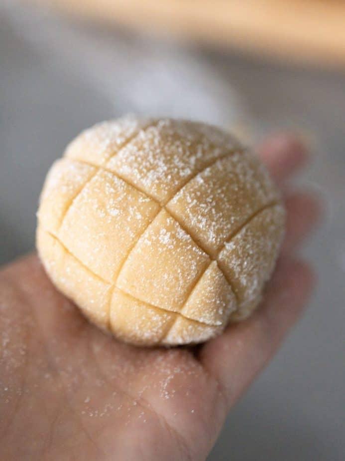 A sugar coated melon bread with a cut design.
