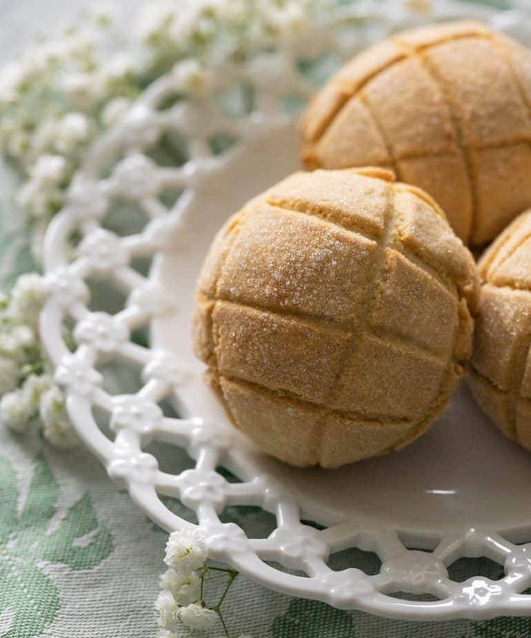 Melon bread on a white plate with flowers and a green cloth napkin.