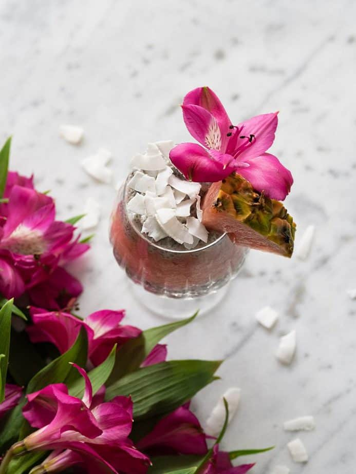 An overhead shot of a coconut flake topped glass by pink, tropical flowers.