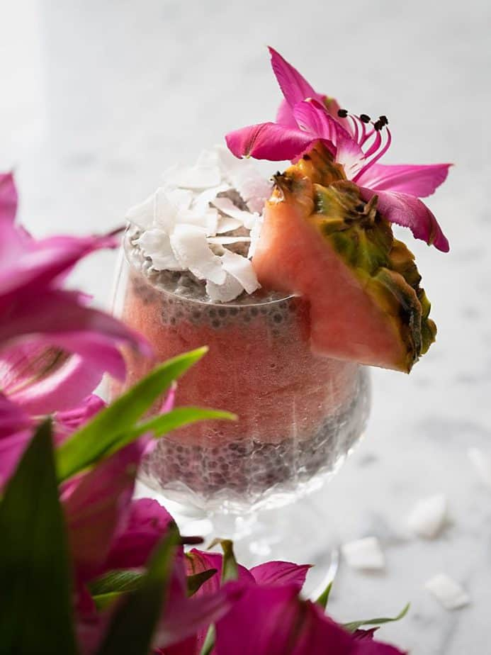 Pineapple coconut chia pudding in a glass by pink, tropical flowers.