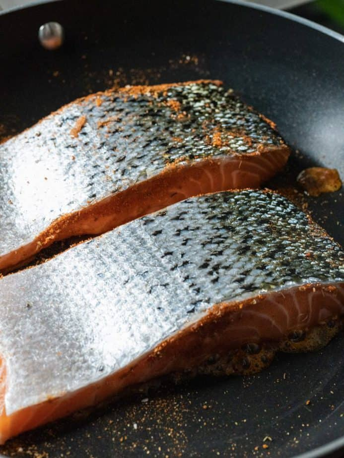Salmon fillets searing in a skillet, skin-side up.