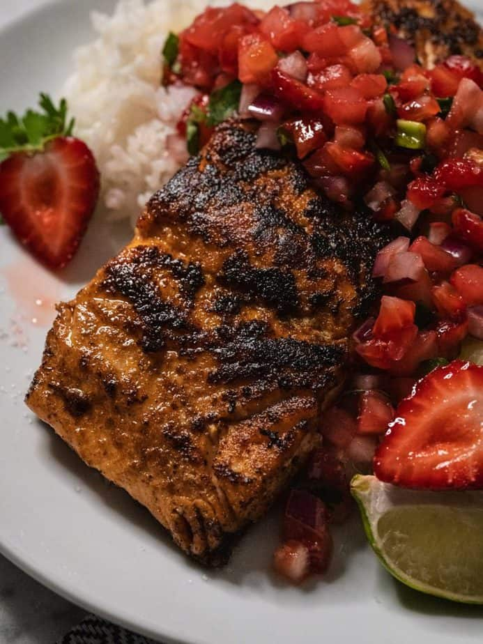 A close up of blackened salmon on a bed of rice topped with strawberry pineapple salsa.