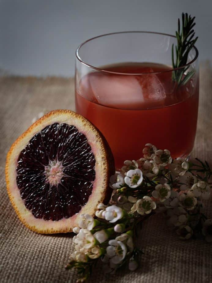 A blood orange negroni with an orange slice and white flowers.