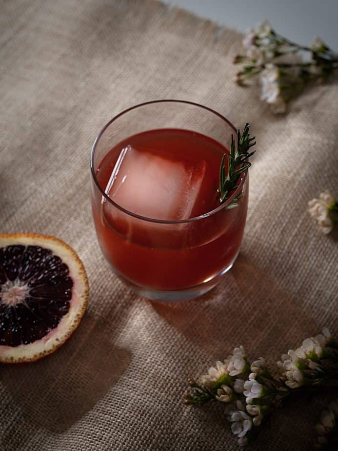 A blood orange negroni and white flowers on a woven fabric.