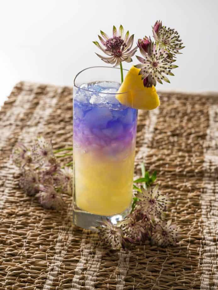 A purple and yellow Royal Hawaiian cocktail on a woven mat.