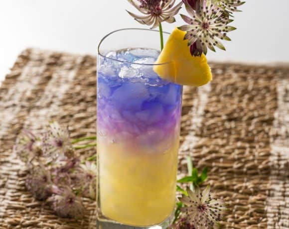 Royal Hawaiian cocktail garnished with flowers and a wedge of pineapple.
