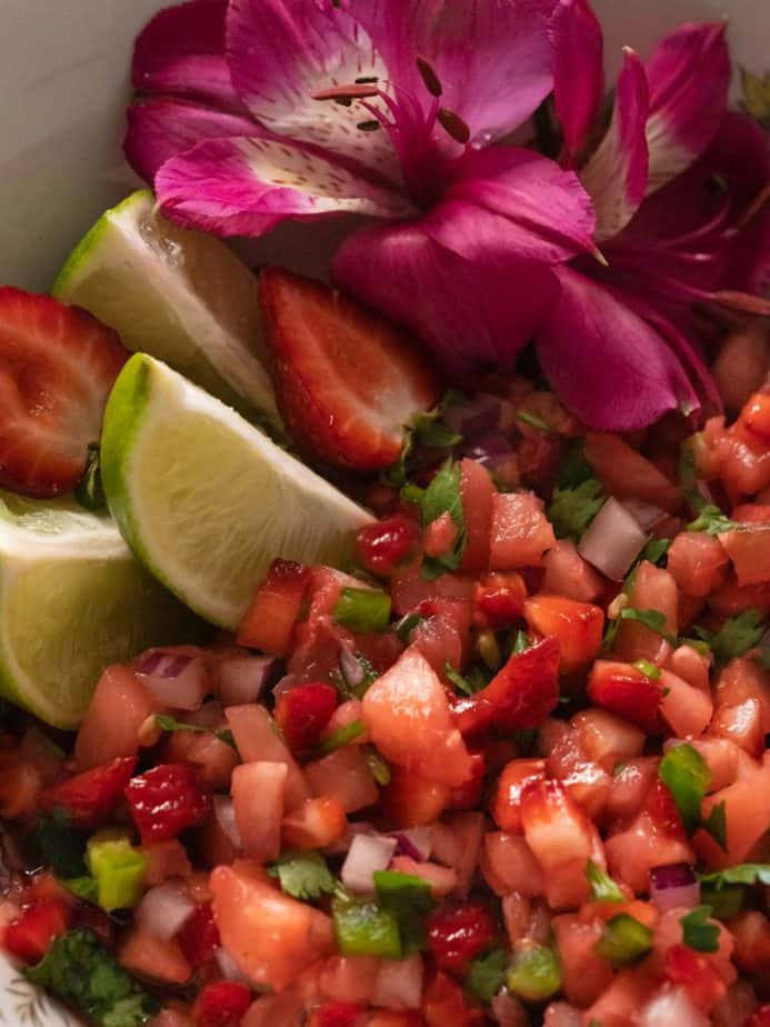 A close up of strawberry pineapple salsa in a bowl with lime wedges and pink flowers.