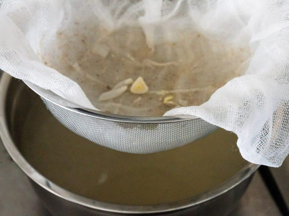 Beef broth is strained through cheese cloth to remove vegetables and impurities.