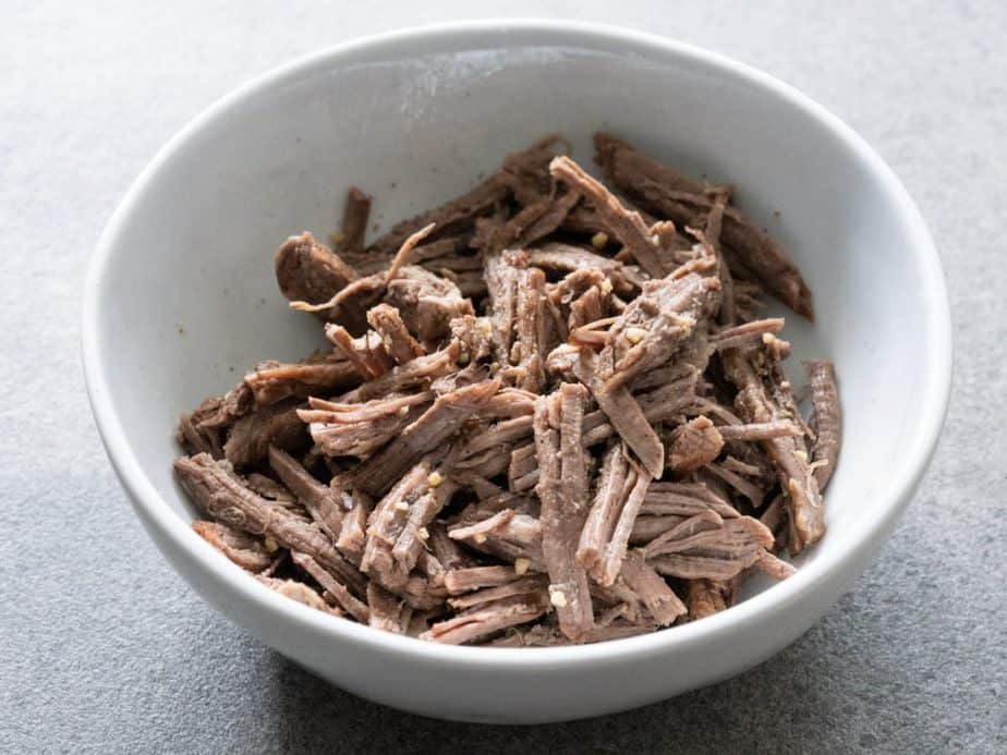 The shredded beef brisket is seasoned with sesame oil, minced garlic, salt and pepper in a bowl.