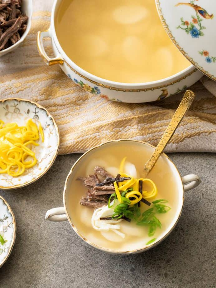 A bowl of Korean rice cake soup and its toppings.