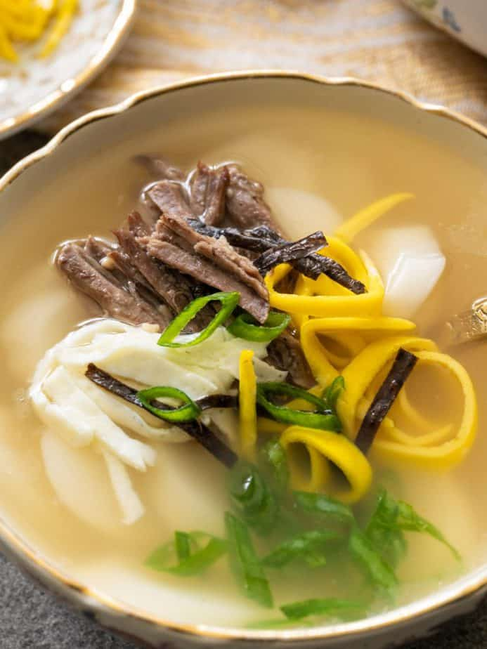 A close up of toppings on a bowl of Korean rice cake soup.